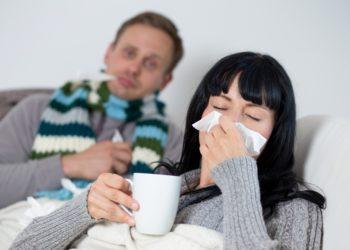 Mann mit Schal und Frau mit Teetasse und Taschentuch liegen zusammen auf dem Sofa