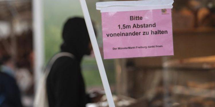 Ein Mann kauft auf dem Markt ein. Am Stand ist ein Schild angebracht mit der Aufschrift «Bitte 1,5 m Abstand voneinander zu halten».