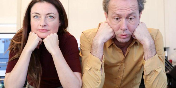 Ein Mann und eine Frau sitzen genervt nebeneinander.