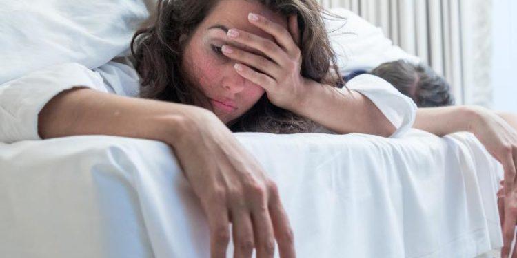 Eine Frau liegt im Bett und hält sich die Hand vor das Gesicht.