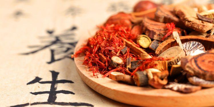 Chinesische Heilkräuter liegen auf einem Holzteller.