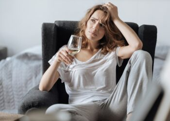 Frau sitzt mit einem Glas Weißwein im Sessel und rauft sich die Haare