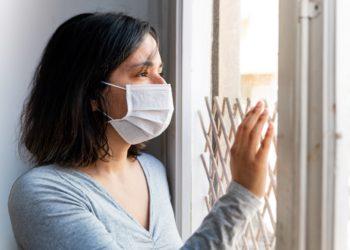 June Frau mit Mund-Nasen-Schutz sieht aus dem Fenster