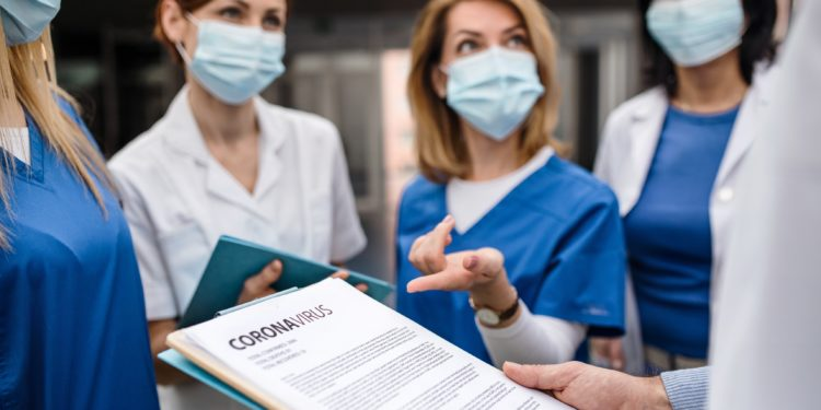 Ärztinnen und Ärzte mit Mundschutz bei einer Besprechung.