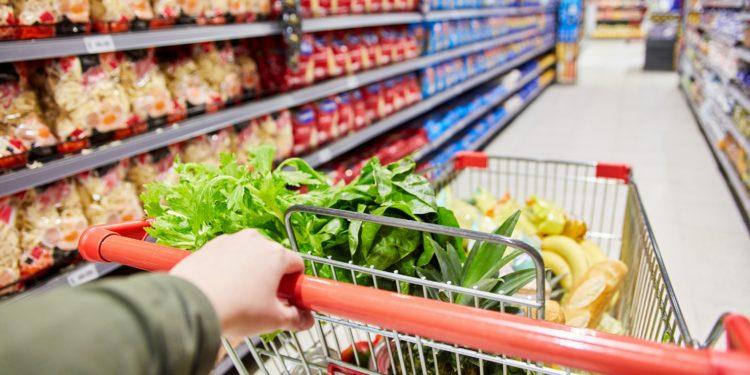 Kunde schiebt Einkaufswagen durch den Gang eines Supermarkts