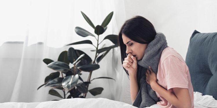 Hustende Frau mit Halstuch sitzt im Bett