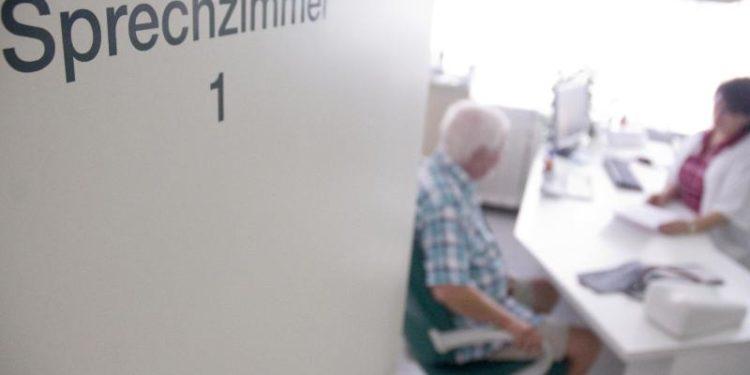 Ein Mann sitzt in einem Sprechzimmer in einer Arztpraxis.