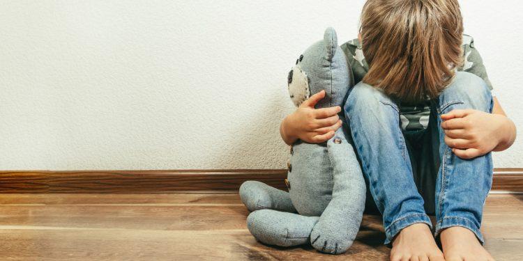 Kleiner Junge sitzt auf dem Boden, mit dem Kopf auf den Knien, hält einen Teddy im Arm