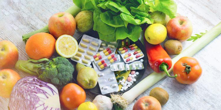 Einige Nahrungsergänzungsmittel liegen zwischen frischem Obst und Gemüse.