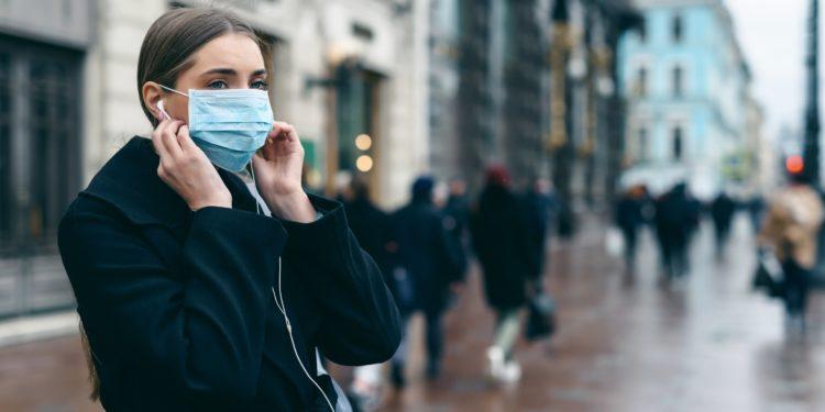 Eine Frau trägt eine Mund-Nasen-Schutzmaske in einer Innenstadt.