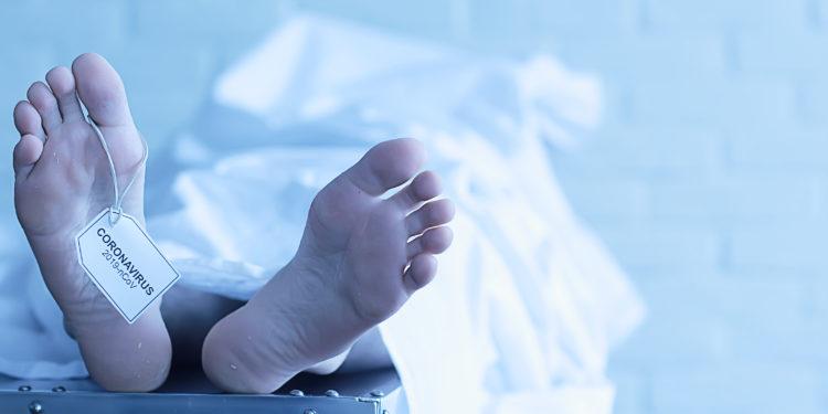 Eine Person liegt auf einer Liege und ist mit einem weißen Tuch zugedeckt.