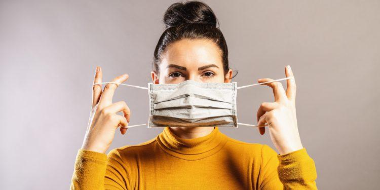 Junge Frau legt eine Mundschutzmaske an