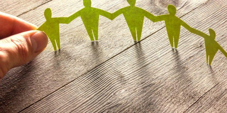 Menschen aus grünem Papier halten sich an den Händen, am linken Ende fassen Daumen und Zeigefinger einer echten linken Hand die Hand einer Papierfigur