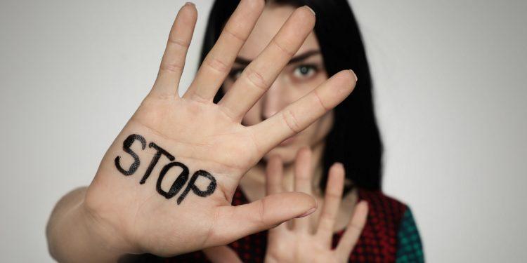 Frau hält ihre rechte Handfläche vor das Gesicht, auf der STOP geschrieben steht