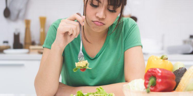 Eine Frau stochert appetitlos in ihrem Essen herum.