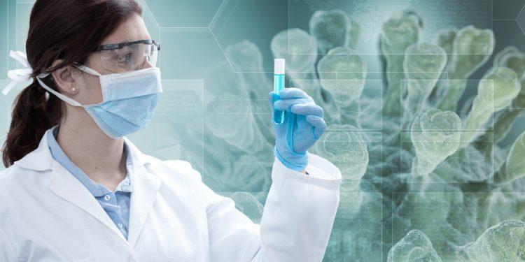 Eine Wissenschaftlerin betrachtet ein Reagenzglas.