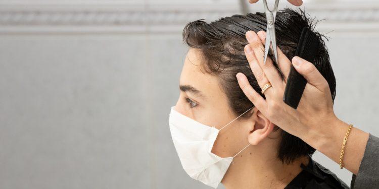 Einem Jugendlichen mit Mund-Nasen-Bedeckung werden die Haare geschnitten