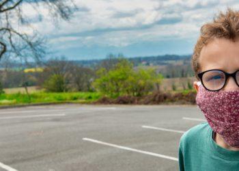Junge trägt im Freien eine Mund-Nasen-Bedeckung