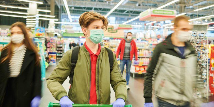 Mann mit Schutzmaske, Handschuhen und einem Einkaufswagen im Supermarkt