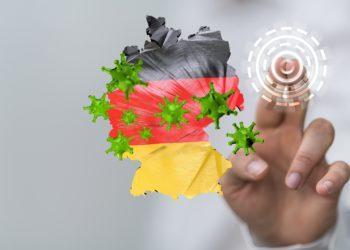 Eine Deutschlandkarte in den Farben der deutschen Flagge, auf der Coronaviren abgebildet sind.