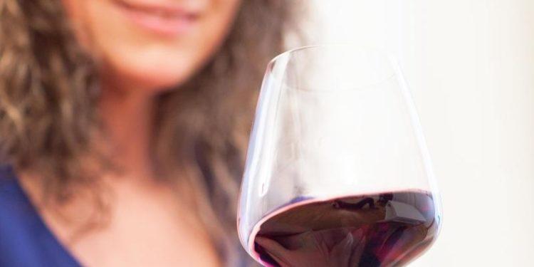 Eine Frau hält ein Glas mit Rotwein in der Hand.