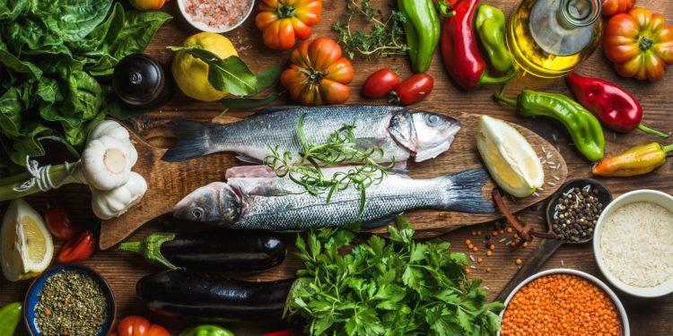 Fisch, Gemüse und Früchte sind auf einem hölzernen Untergrund drapiert.