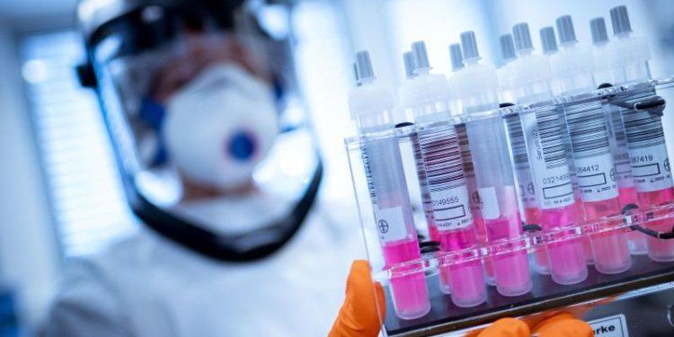 Eine Person im Schutzanzug betrachtet einige Labor-Proben.