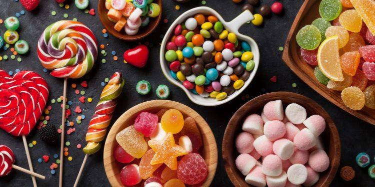Verschiedene Süßwaren liegen auf einer dunklen Oberfläche.