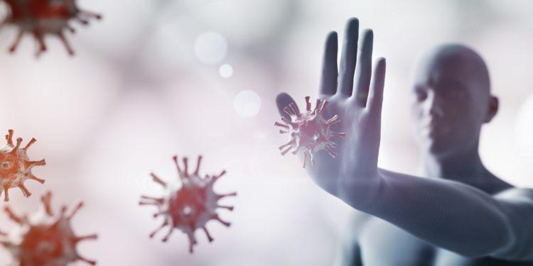 Ein Mann wehrt mit der Hand auf ihn zu kommende Viren ab.
