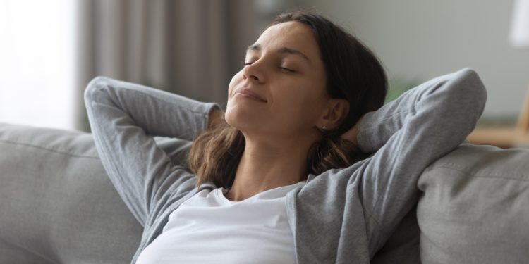 Eine Frau sitzt mit geschlossenen Augen und hinter dem Kopf verschränkten Armen auf dem Sofa und entspannt sich.