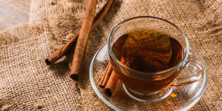 Eine Tasse mit Zimt-Tee und zwei Zimtstangen auf einem Jutesack.