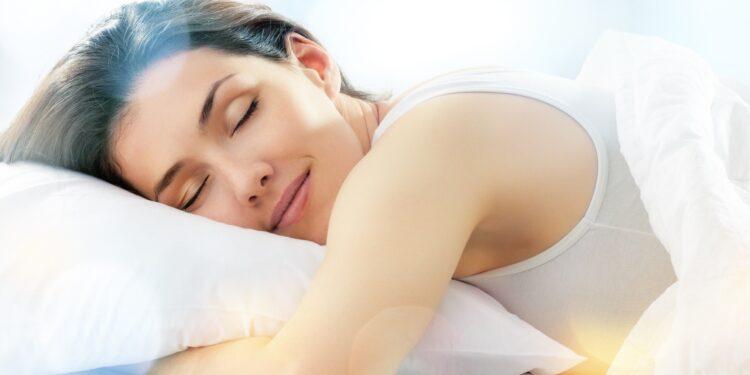 Eine Frau schläft und macht dabei einen zufriedenen Gesichtsausdruck.