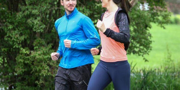 Ein Mann und eine Frau joggen zusammen und unterhalten sich dabei.