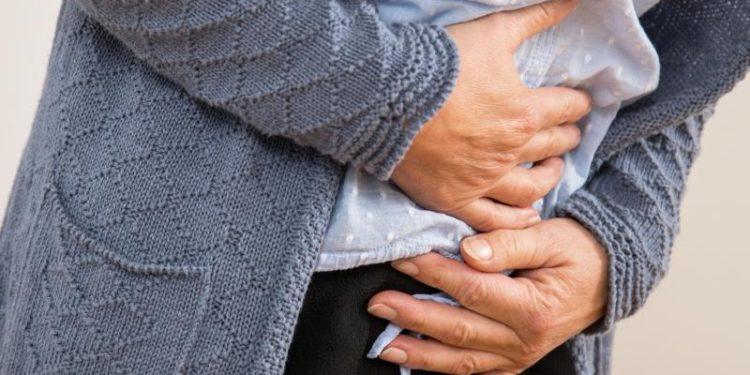 Eine Frau hält sich beide Hände auf den Bauch und den Unterleib.