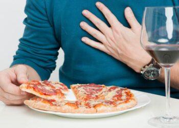 Ein Mann fasst sich auf die Brust, während er eine Pizza isst.