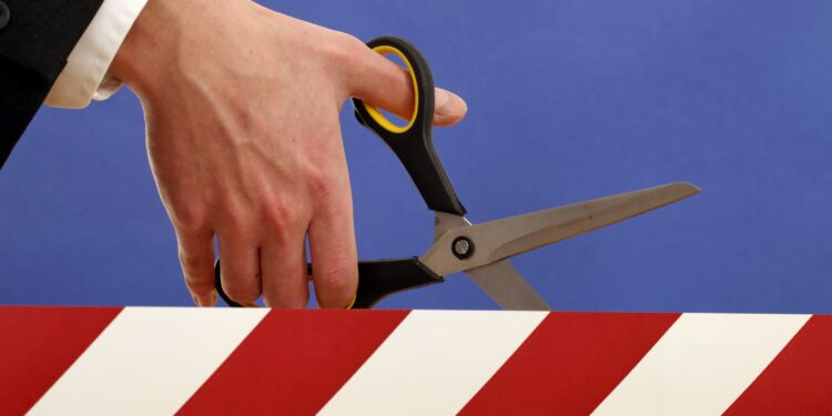 Eine Person schneidet mit einer Schere ein Absperrband durch.