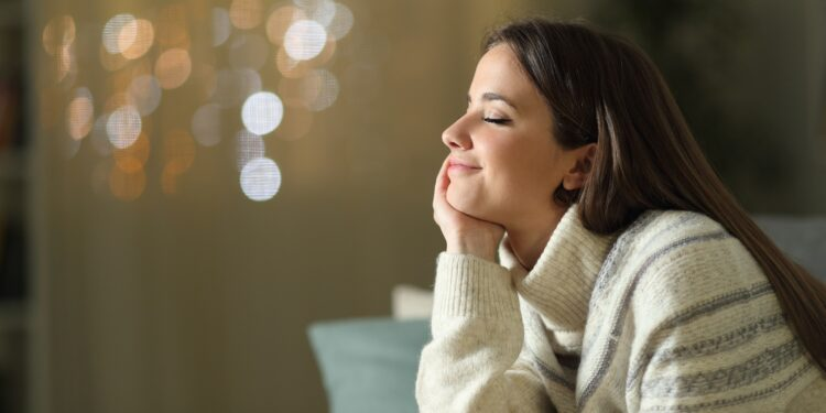 Entspannt lächelnde Frau sitzt auf dem Sofa