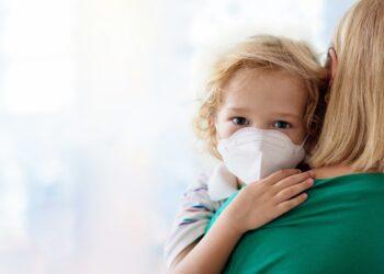 Kind mit Mundschutz auf dem Arm der Mutter
