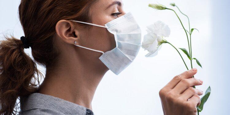 Eine Frau mit Mund-Nasen-Schutz riecht an einer Blume