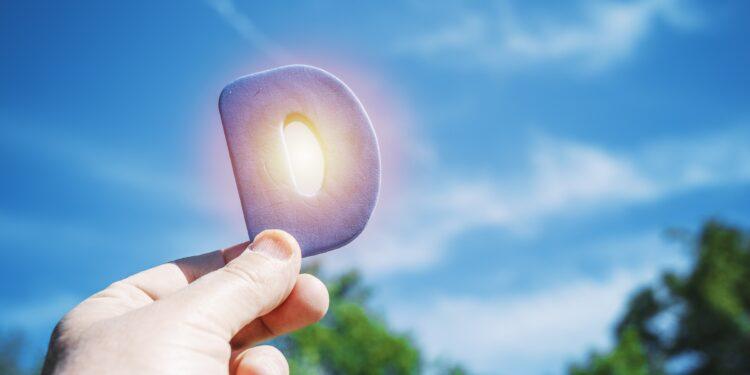 Eine Hand hält den Buchstaben D vor die Sonne.