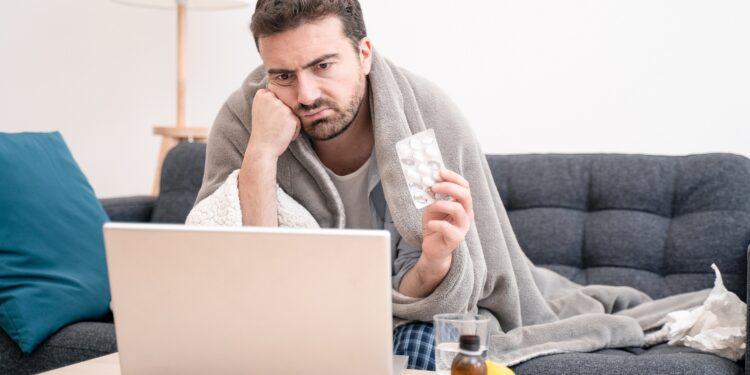 Ein kränklich aussehender Mann schaut auf einen Laptop.