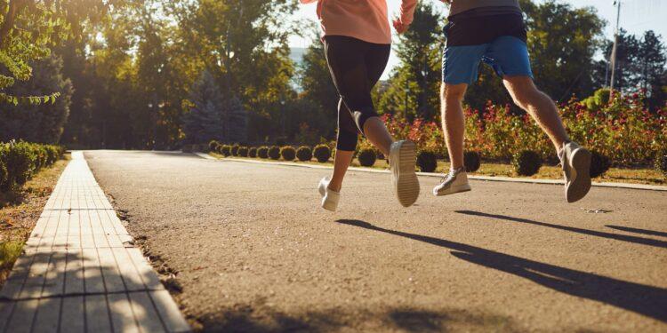Ein Mann und eine Frau rennen morgens die Stadtstraße entlang