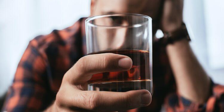 Deprimierter Mann mit einem Glas Whiskey