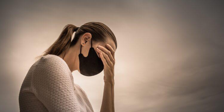 Frau mit Mund-Nasen-Schutz verdeckt besorgt ihre Augen