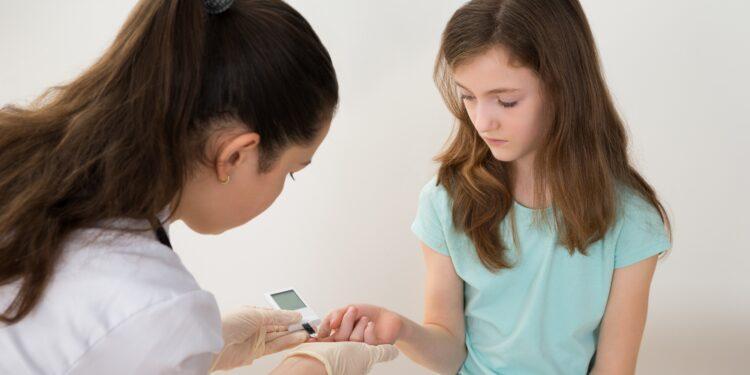 Ärztin misst bei einem Mädchen den Blutzucker