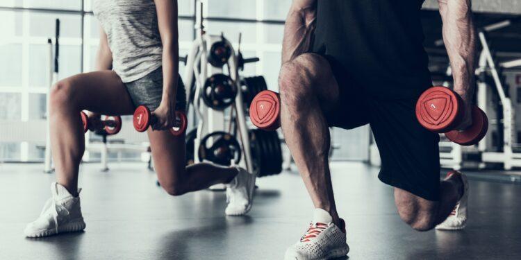 Frau und Mann trainieren im Fitnessstudio mit Hanteln