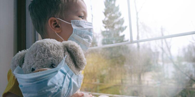 Ein junge mit Mund-Nasen-Schutzmaske sitzt am Fenster.