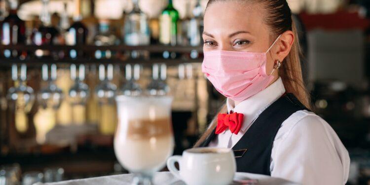 Eine weibliche Bedienung mit Mund-Nasen-Schutz serviert Kaffee