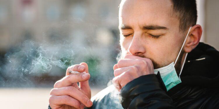 Mann mit Zigarette und umgehängten Mund-Nasen-Schutz hustet in seine Hand