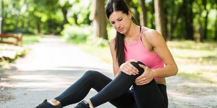 Läuferin sitzt im Park auf dem Boden und hält ihr schmerzendes Knie